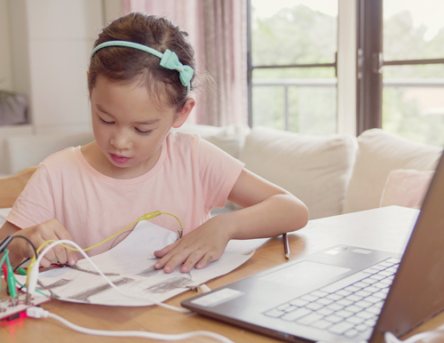 child learning at home via laptop